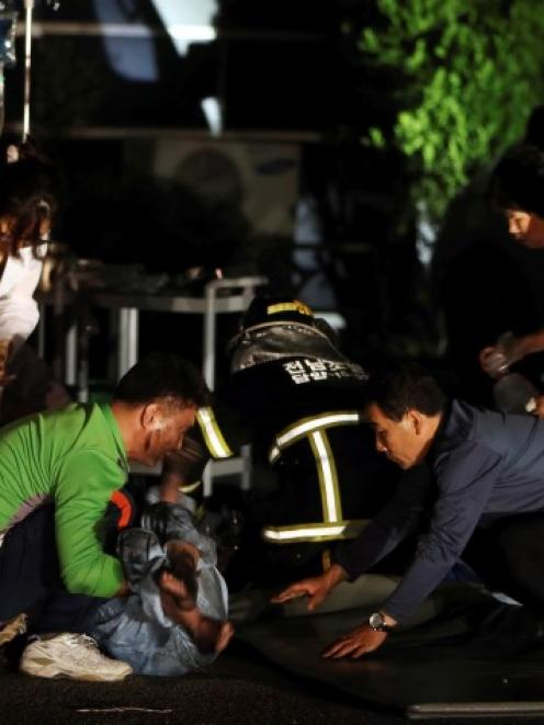 Hospital officials attend to a patient rescued from the fire. REUTERS/Hyung Min-woo/Yonhap