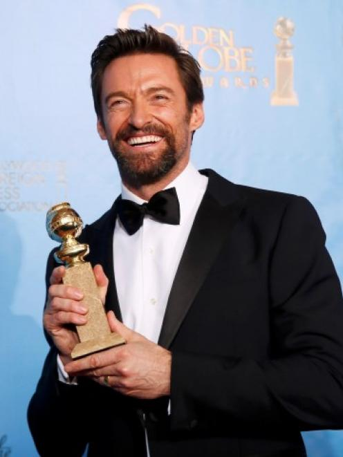 Hugh Jackman holds up the award he won for Best Performance in a musical or comedy for his...