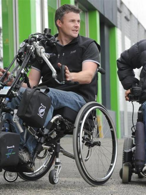 Importer Shanon Arnold (left) in the Striker hand bike with tetraplegic Keith Jarvie, who is...