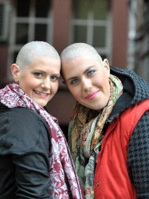 Caitlin Dunstan-Harrison (left) and Hannah Langford-Berman, with their freshly-shaved heads, pose...