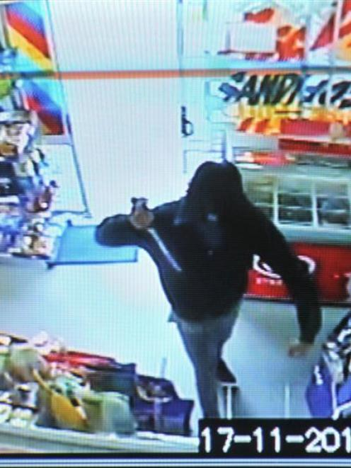 In this still shot from CCTV footage, a man brandishes a large knife during the robbery of a...