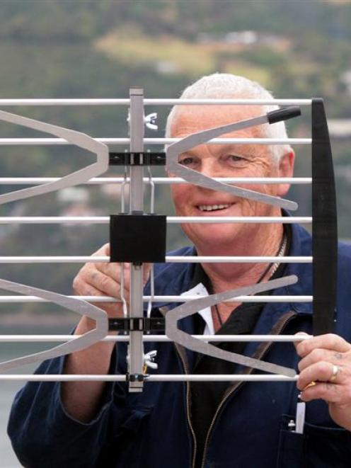 In tune . . . Aerial and television installer Ross Griffiths holds up a new high definition UHF...