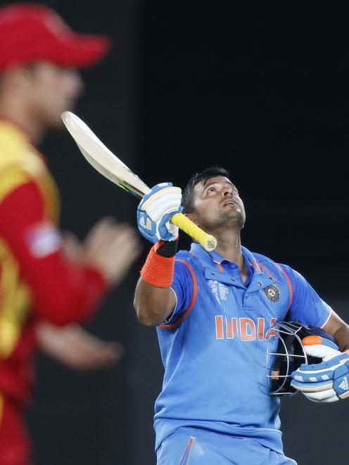 India's Raina celebrates scoring a century during their Cricket World Cup match against Zimbabwe...