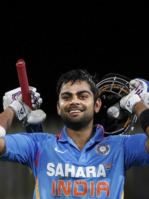 India's Virat Kohli celebrates reaching his century during their Tri-series one-day international...