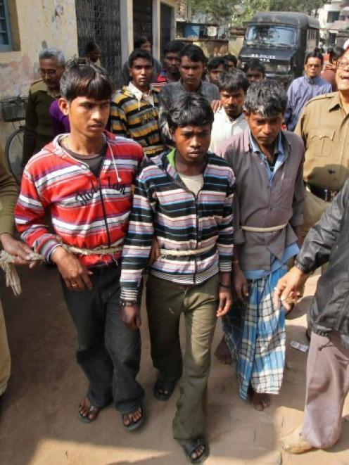 Indian police personnel escort men (tied with rope) accused of the gang-rape to a court at...