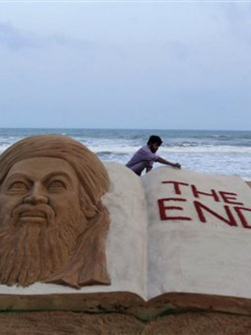 Indian sand artist Sudarshan Pattnaik gives finishing touches to a sand sculpture to mark the...