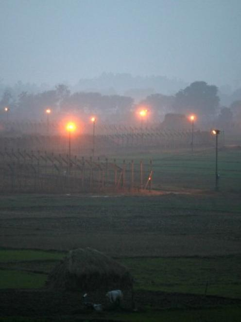Indian security posts (R) are seen along the border between India and Pakistan in Suchetgarh,...