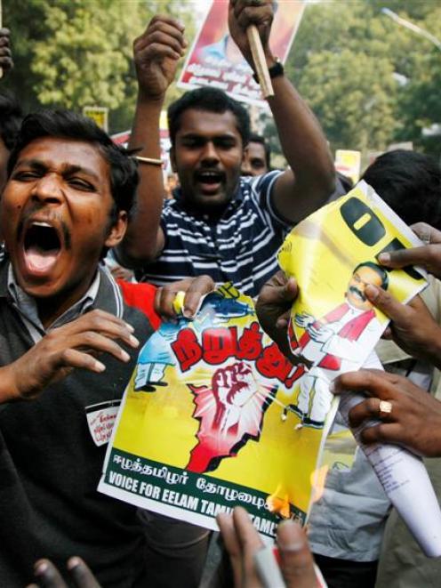 Indian Tamils tear and burn a poster of Sri Lankan President Mahinda Rajapaksa and Indian Prime...