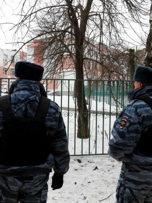 Interior Ministry members stand guard outside the premises of the high school after the shooting....
