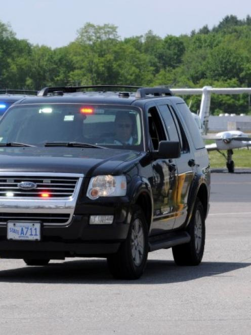 Investigators from the State Fire Marshal's Office leave the scene of the crash at Hanscom Field...
