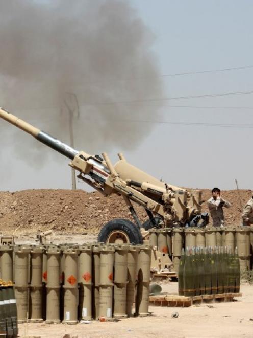 Iraqi security forces fire artillery during clashes with ISIL forces on the outskirts of the town...