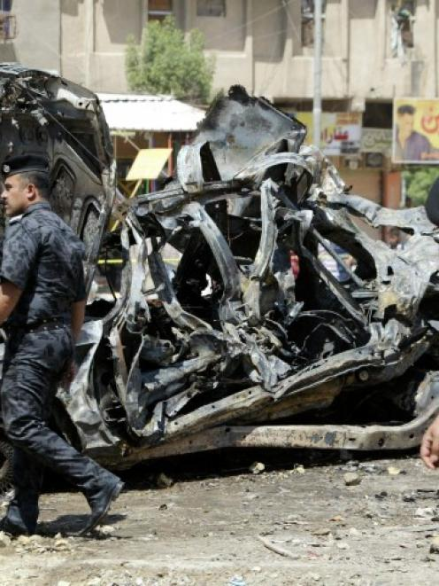 Iraqi security forces walk past damaged vehicles as they inspect the site of a car bomb attack in...
