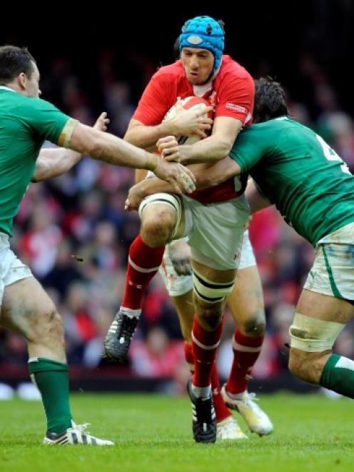 Ireland players tackle Wales' Scott Williams during their match at the Millennium Stadium in...