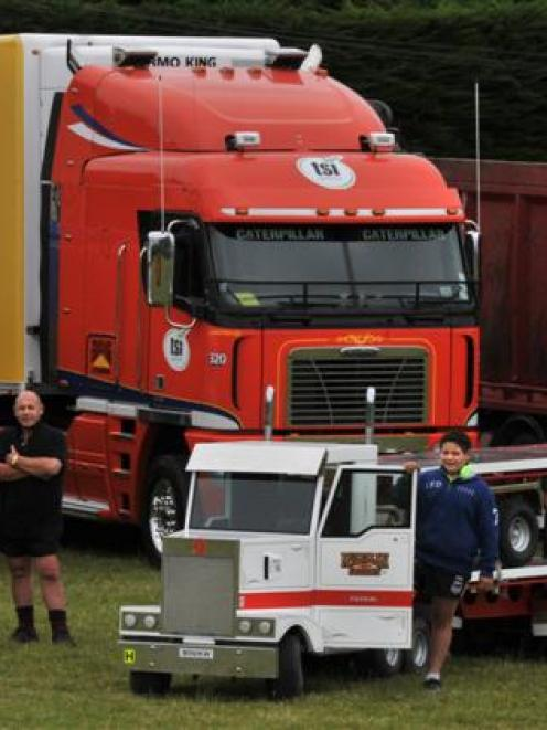 Isaiah McLellan (13) shows off a miniature Kenworth 904 built by his father, Alex (centre). The...