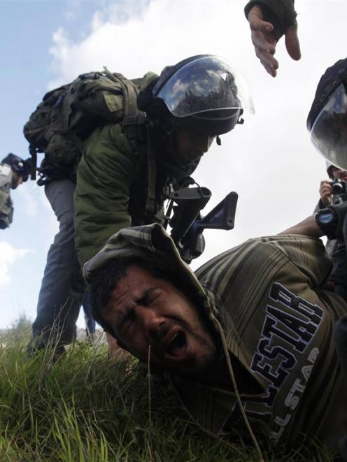 Israeli border police detain a Palestinian man after a group of activists set up tents and...
