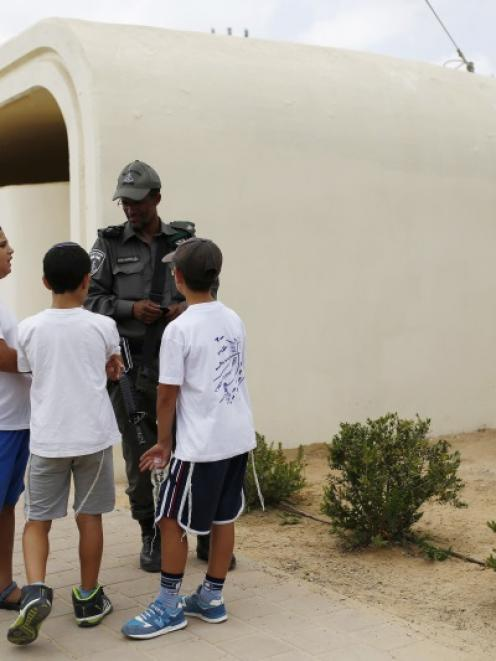 Israeli children speak with a police officer as they stand next to a bomb shelter on the first...
