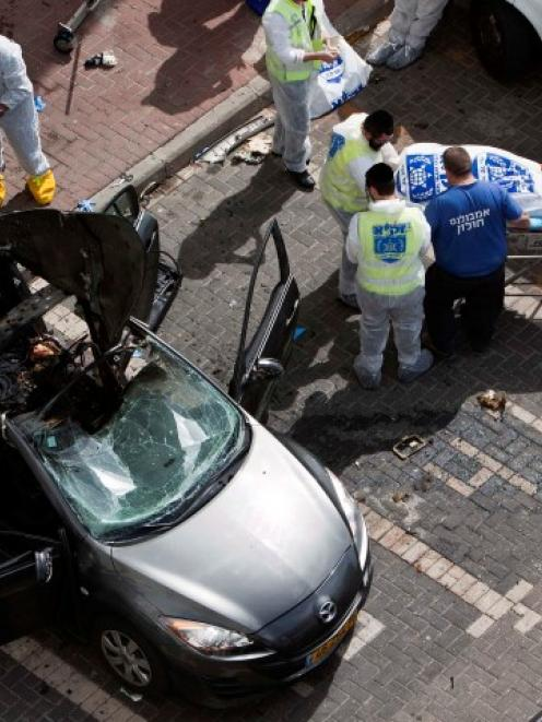 Israeli emergency personnel wheel away a body from the scene of an explosion near Tel Aviv in ...