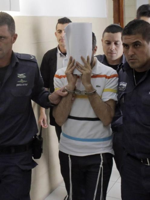 Israeli prison guards lead one of three Israeli defendants in the murder of Palestinian youth...