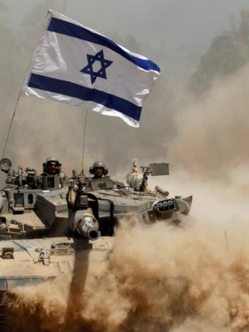 Israeli soldiers ride a tank after returning to Israel from Gaza. REUTERS/Siegfried Modola