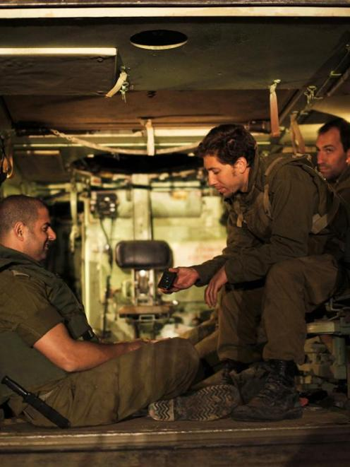 Israeli soldiers sit in an Armoured Personnel Carrier (APC) at a staging area outside the...