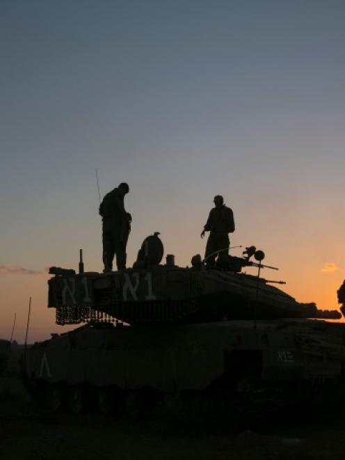 Israeli soldiers stand on top of a tank near the Israeli border with the Gaza Strip. REUTERS/Baz...