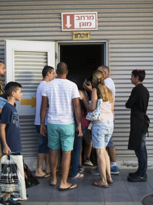 Israelis enter a bomb shelter as a siren sounds warning of incoming rockets in Ashkelon. Photo by...