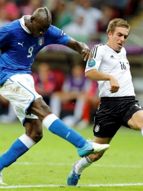 Italy's Mario Balotelli scores his second goal despite the attentions of Germany's Philipp Lahm....