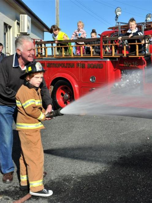 Jack Thom, of Mt Cargill, and his grandfather, ex-Waikouaiti firefighter Allan Black, use a  hose...