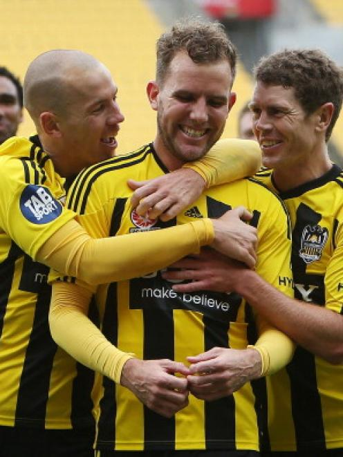 Jeremy Brockie of the Phoenix is congratulated on his goal by teammates Stein Huysegems and Tony...