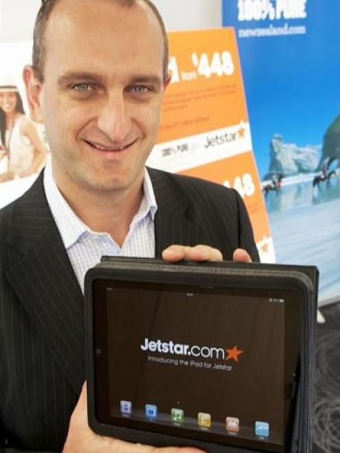 Jetstar Group chief executive Bruce Buchanan holds one of the Apple iPads the airline will offer...