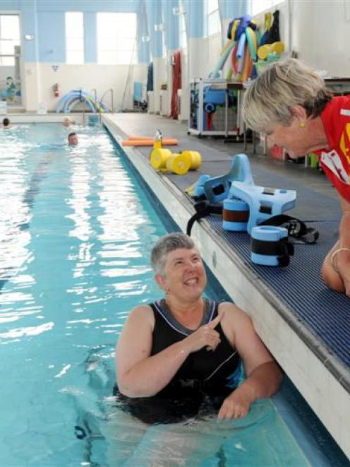 Jill Chalmers catches up with therapeutic pool supervisor Robyn Duggie during her swim in the...