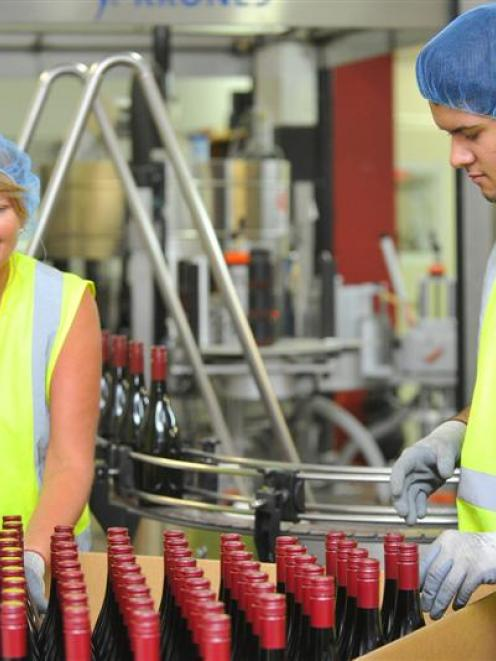 Jo Lunn and Riley Fraser, both of Cromwell, pack freshly bottled wine at VinPro in Cromwell on...
