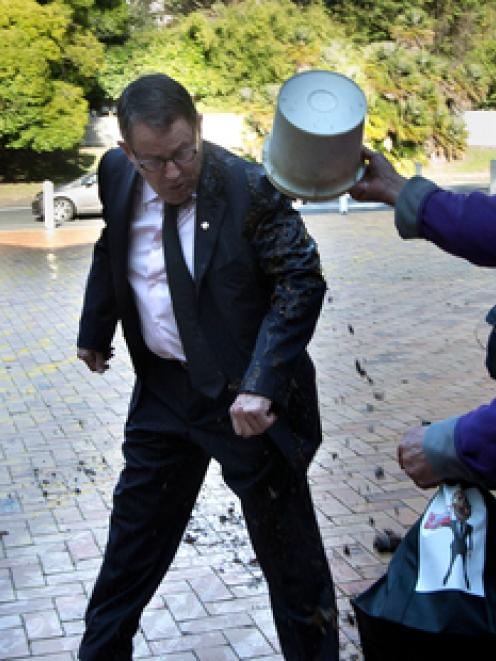 John Banks is attacked with a bucket of mud, as he arrives at the High Court in Auckland this...
