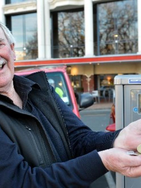John Simpson, of Christchurch, with the coins that poured out of a Dunedin parking machine...