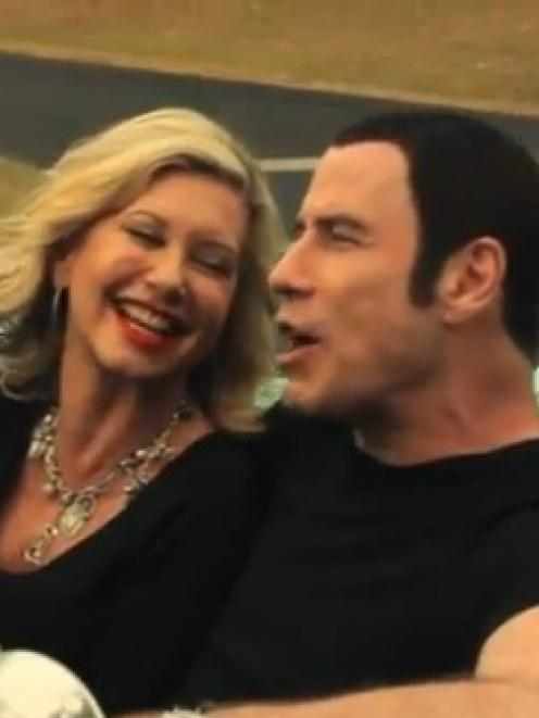 John Travolta and Olivia Newton John appear in the video for 'I Think You Might Like It', from...