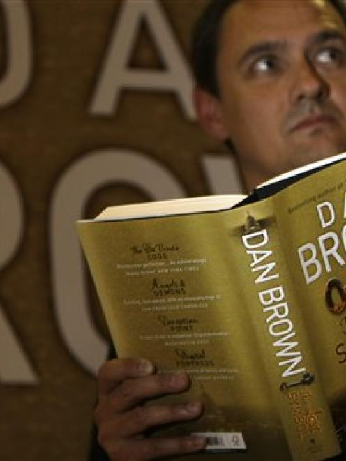 Jon Howells,  press officer for Waterstone's booksellers,  poses for the cameras as he reads a...