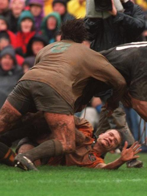 Jonah Lomu scores in the tackle of Ben Tune (on ground) and Daniel Herbert at Athletic Park in...