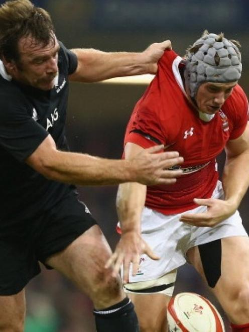 Jonathan Davies of Wales spills the ball under the challenge of Andrew Hore whose act of...