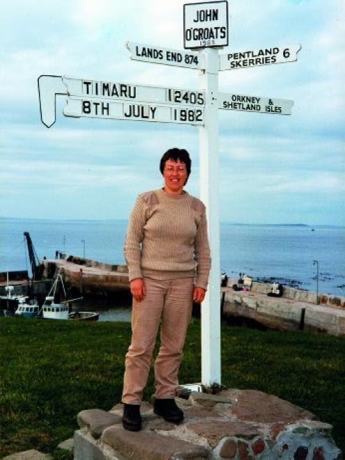 Jude Wilson poses under a personal embellishment on the signpost at John O'Groats, Scotland, in...