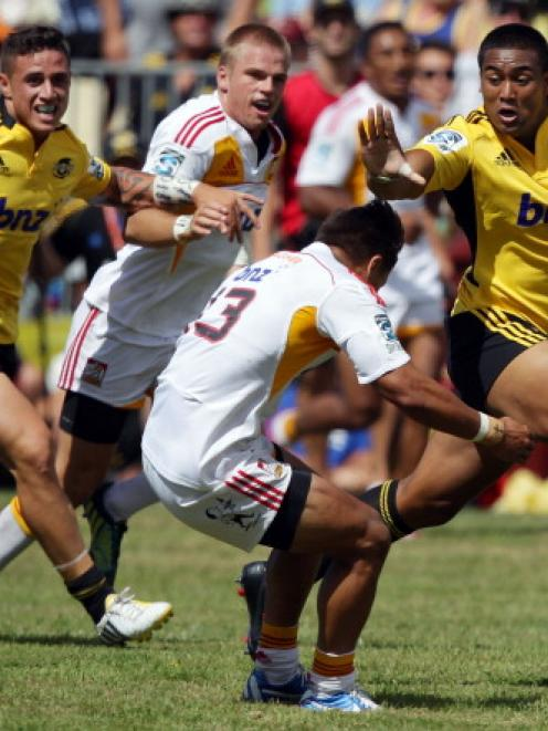 Julian Savea of the Hurricanes fends Tim Nanai-Williams of the Chiefs. (Photo by Hagen Hopkins...