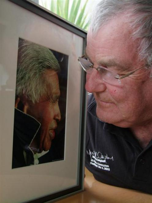 Kaka Point resident Norman Woods looks fondly at a photograph of the late poet Hone Tuwhare, who...