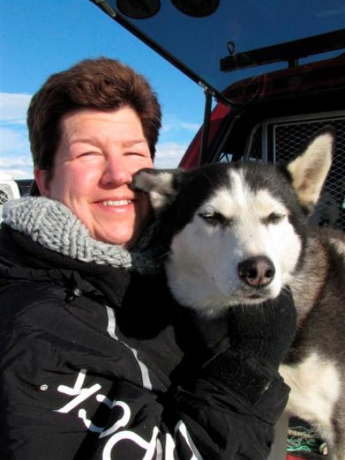 Karen Ramstead, of Canada, inspects Siberian husky Aladdin (8), of Clyde, before the start of the...