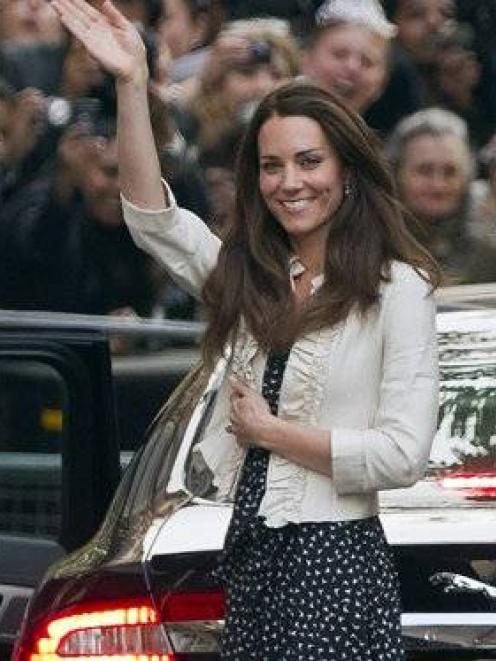 Kate Middleton waves to the crowds gathered outside the Goring Hotel in London yesterday ahead of...