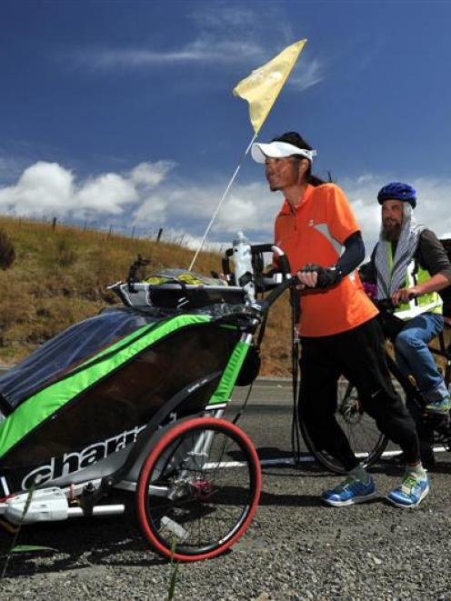 Katzhiko Takashige, of Japan, accompanied by Paul Gourlie, of Dunedin, makes his way up the...