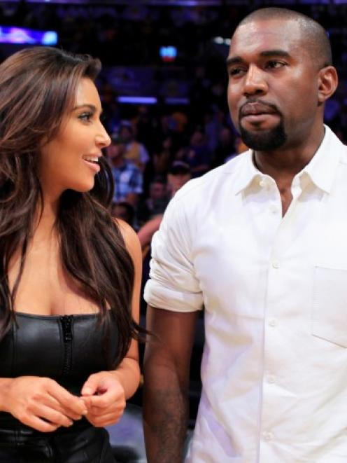 Kim Kardashian (L) and attend a Los Angeles Lakers basketball game in May. The pair are expecting...