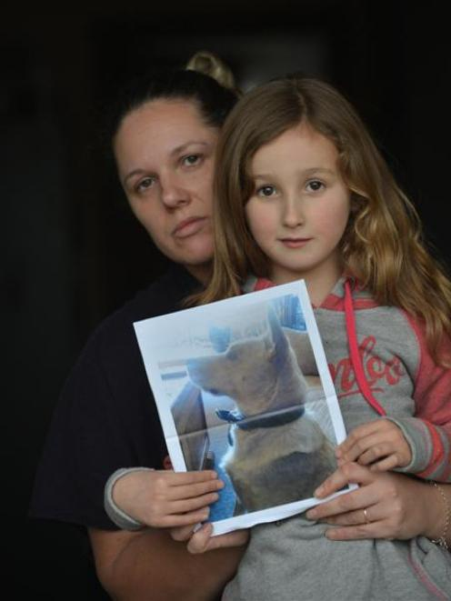 Kimberly and Maia Allen (5), of Dunedin, hold a picture of their dead dog Obi. Photo by Peter...