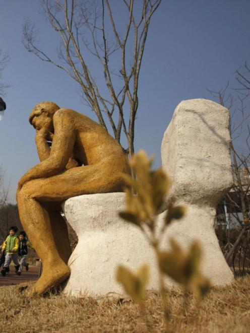Kindergarden children walk past an installation shaped like Auguste Rodin's 'The thinker' sitting...