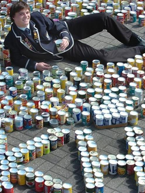 Kings High School student council chairman Sam Brown sits among the 1780 cans of food collected...