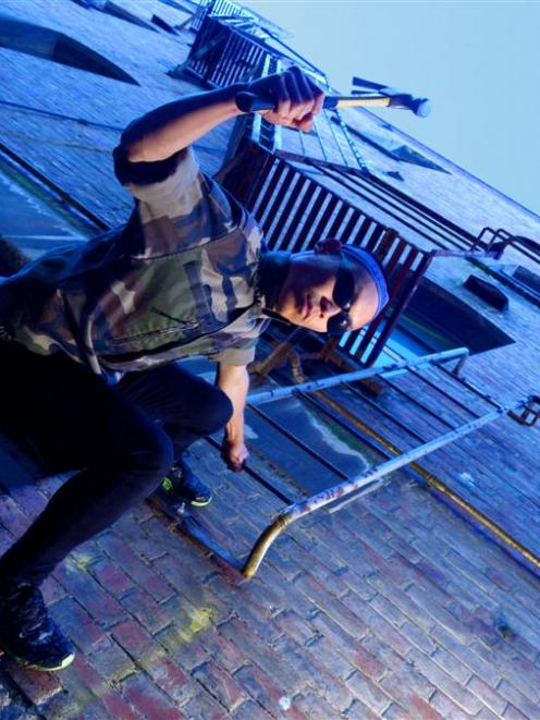 Korean performance artist Samin Son (26) hangs in the alley behind the Blue Oyster Art Project...