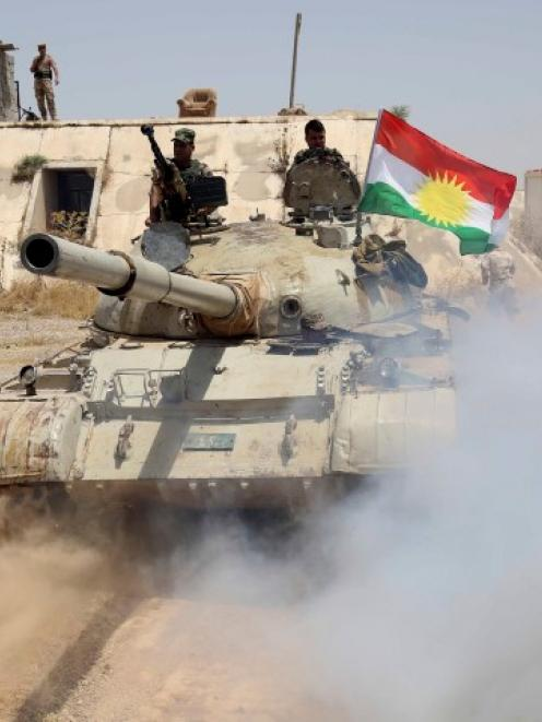 Kurdish Peshmerga troops travel in a tank as they secure an area in the town of Sulaiman Pek in...